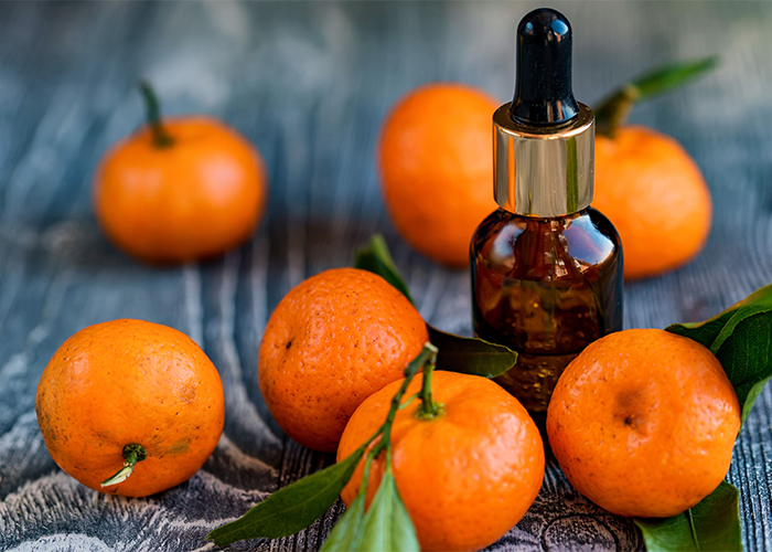 Bottle of mandarin essential oil with a dropper next to a pile of mandarins