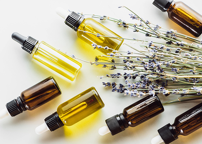 Clear and amber colored bottles filled with bergamot essential oil lavender essential oil, and lemon essential oil next to sprigs of dried lavender