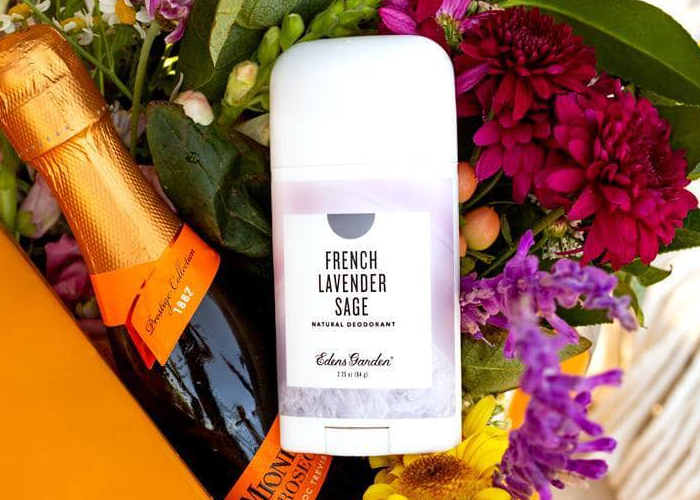 Edens Garden French Lavender Sage natural deodorant on top of a crate of flowers and champagne