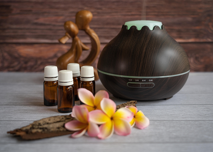 A variety of essential oils next to a wooden essential oil diffuser