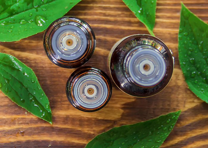 A top-down shot of essential oil bottles filled with tea tree essential oil