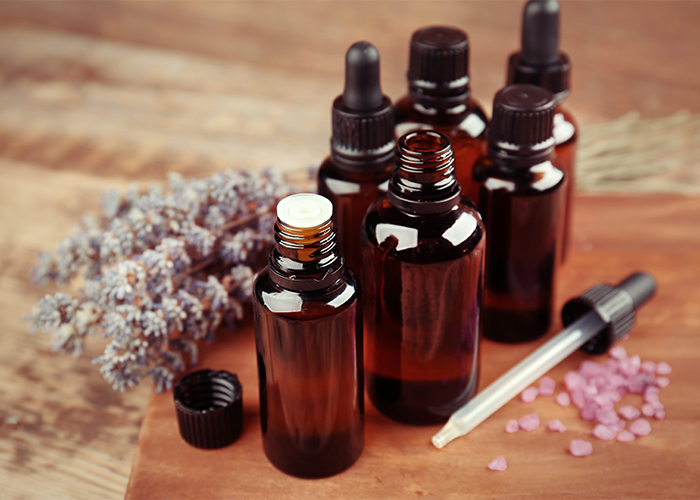 Different types of amber bottles filled with lavender essential oil on a wooden board