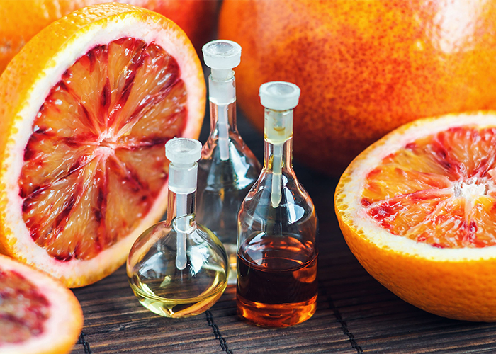 Small bottles of orange essential oil surrounded by freshly cut blood oranges