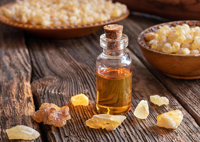 A  bottle with a cork stopper filled with frankincense essential oil next to bowls of frankincense