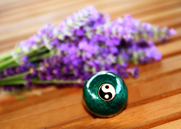 Focus on a green ball for relaxation with the Chinese yin and yang sign with sprigs of lavender in the background