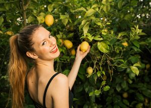 Woman smiling as she looks back while picking a lemon off of a lemon tree