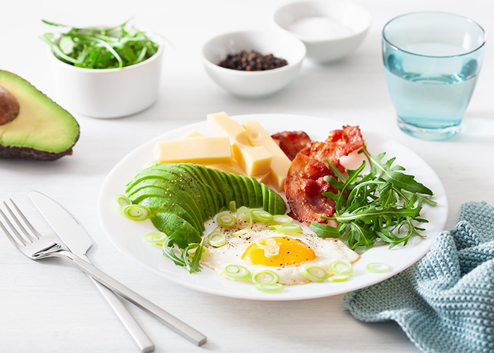 A healthy Keto breakfast plate with sliced avocados, sunny side up eggs, wild arugula, cheese, and chili flavored bacon