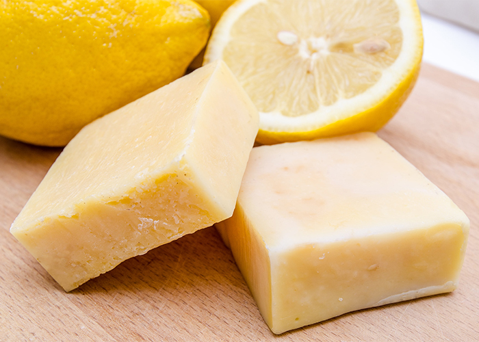 Homemade antibacterial manuka soap on a wooden board with lemons