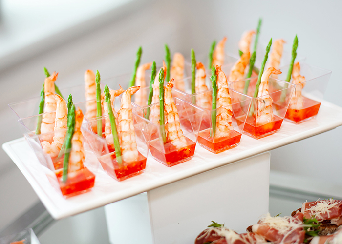 A plate of high-end Keto shrimp appetizers dipped in sweet and sour with a sprig of asparagus