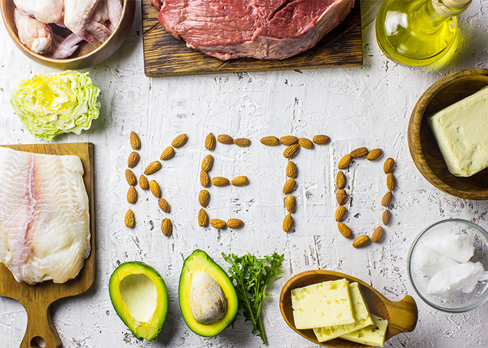 """Typical low-carb foods eaten on the Keto diet surrounding almonds that spell out """"KETO"""""""