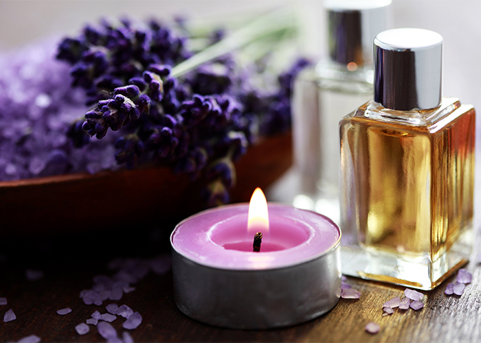 A lavender essential oil tea candle candle next to a pile of lavender bath salt, fresh flowers, and a bottle of perfume