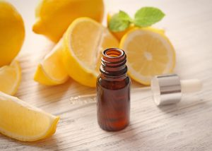 An open bottle of lemon essential oil surrounded by cut and hole lemons
