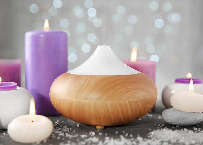 An electric essential oil diffuser surrounded by essential oil candles