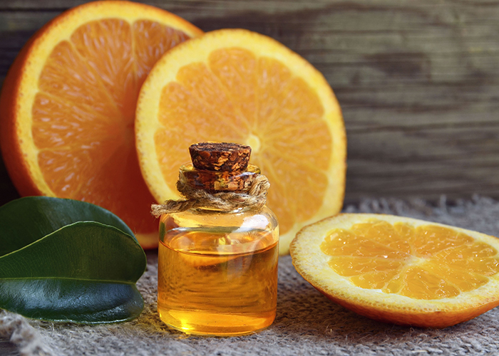 A small bottle of hand-poured orange essential oil with slices of orange in the background