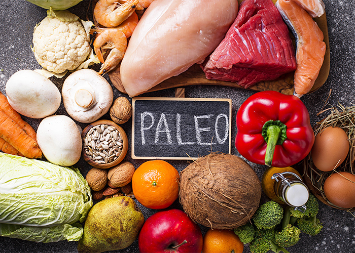 "A top-down view of different foods on the Paleo diet including high protein low carbohydrate foods  like meat, poultry, nuts, vegetables, and fruit surrounding a small blackboard written with the word ""PALEO"""
