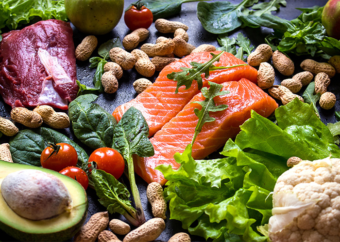 An assortment of different Paleo foods including fish, vegetables, nuts, and fruit