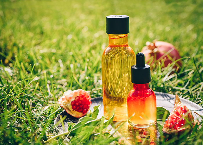 Large and small bottles of pomegranate essential oil next to pieces of pomegranate essential oil on a plate on plate on a grass