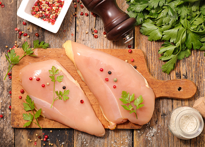 Two raw chicken breasts seasoned with pepper and herbs on a cutting board