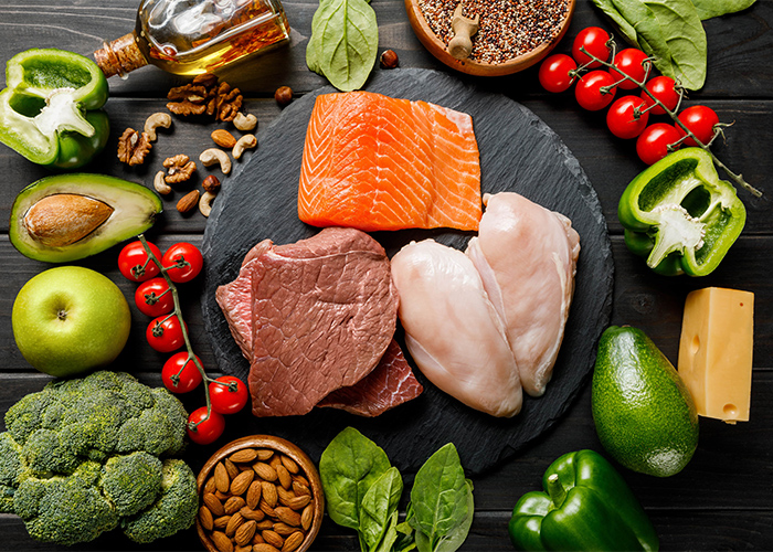 A flat lay of different keto ingredients such as meat, chicken, salmon, fruits, vegetables and nuts