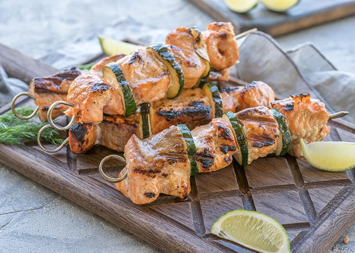 A wooden board with salmon and zucchini kebab skewers with slices of lime