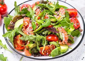 A bowl of salad with smoked salmon, mixed green leaves, tomatoes, and avocados