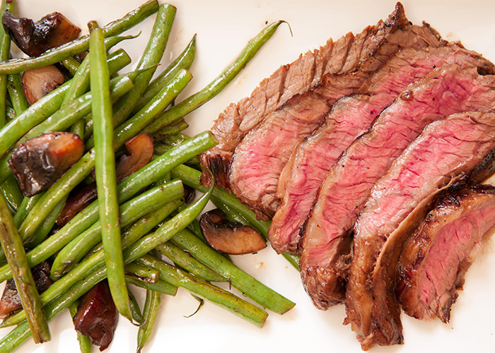 A plate of sliced medium-rare steak next to a side of green beans and mushrooms