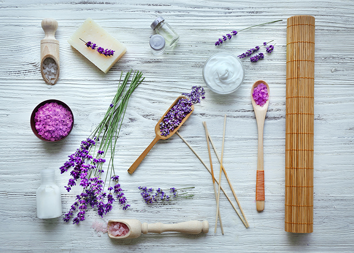 Flat lay of lavender essential oil spa products such as bath salts, moisturizing creams, and soap
