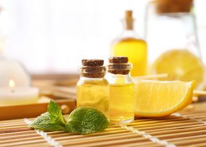 A spa composition of lemon essential oil bottles and fresh slices of lemon