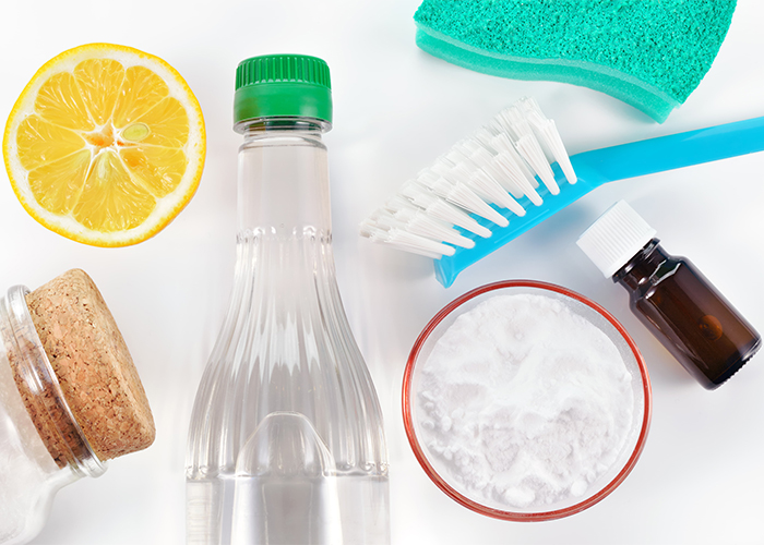 A top-down view of different natural cleaning products such as a bottle of essential oil, lemon, vinegar, and baking soda