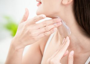 Woman applying manuka essential oil moisturizing cream to her neck.