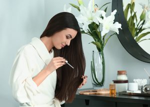Long-haired woman using a dropper to apply an essential oil mix to her hair
