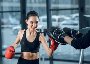 A woman in a boxing class punching the boxing pads her trainer is wearing