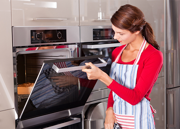 A woman opening her kitchen oven to check whether her dessert is ready