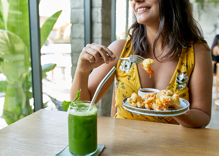 Woman at a fancy restaurant eating Keto-approved shrimp and drinking a green juice
