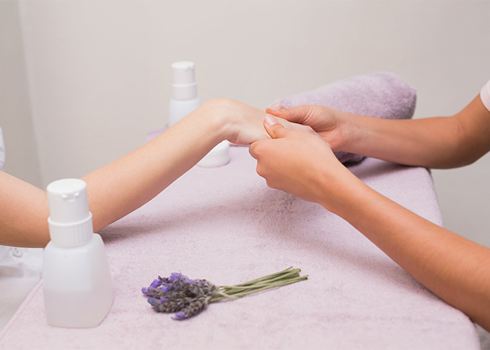 A woman getting a hand massage with lavender essential oil by a masseuse