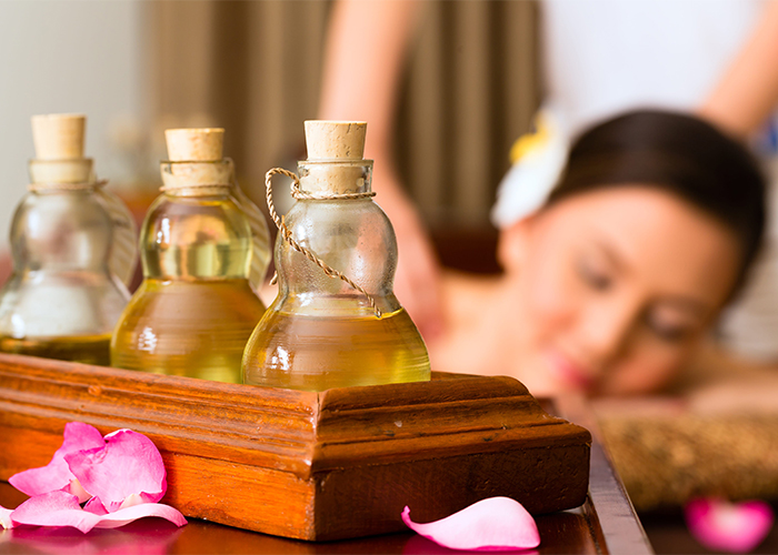 Bottles of essential oil blends for massage with a woman getting a massage in the background with them