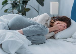 Depressed woman curled up in her bed crying into her hands