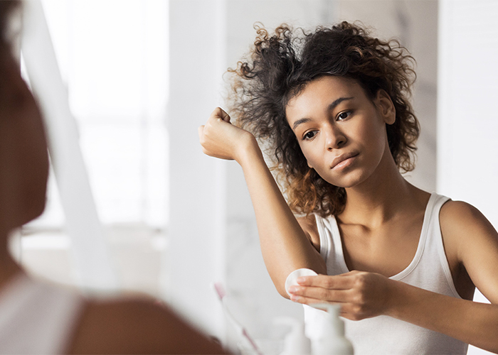 Woman looking in her bathroom mirror while rubbing manuka essential oil on her injured elbow