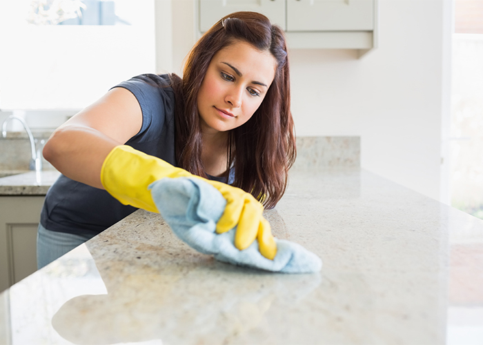 Woman scrubbing her kitchen counter using all-natural bergamot essential oil cleaning spray