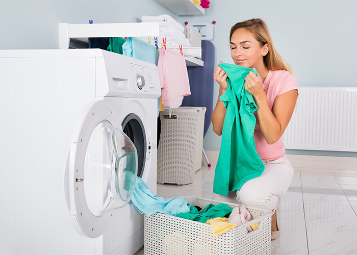 Woman smelling clean laundry that smells like a homemade citrus essential oil blend laundry fragrance