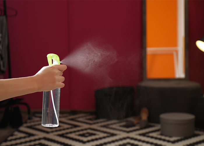 Woman spraying a bergamot essential oil room freshening spray in her home living roo