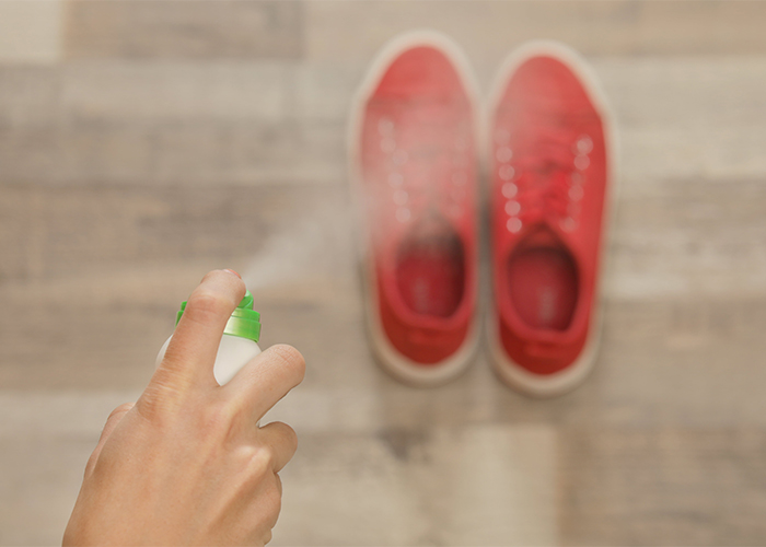 Woman spraying homemade manuka essential oil deodorizing spray on her sports shoes