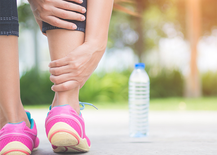 Woman grabbing her ankle in pain while on a run