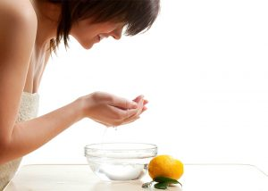 Woman washing her face with a homemade lemon essential oil cleanser