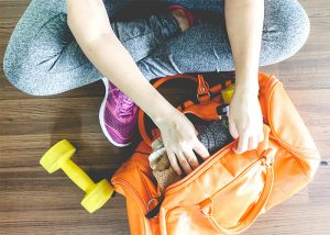A woman packing her gym bag with gym clothes and dumbbells ready for a workout