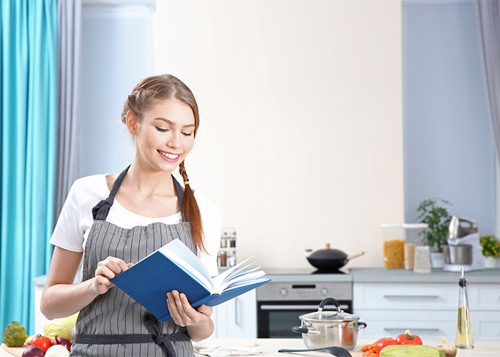 Young woman smiling while reading a Paleo recipe book in her kitchen excited to start cooking
