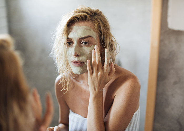 woman-applying-diy-acne-mask-on-her-face-in-bathroom