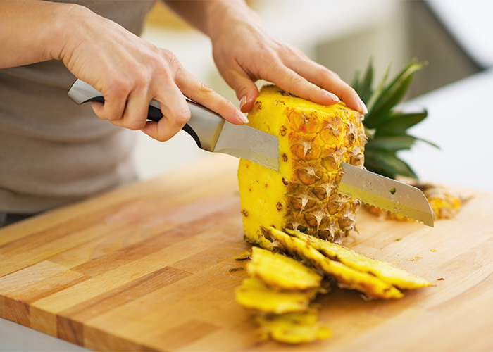 woman-cutting-pineapple