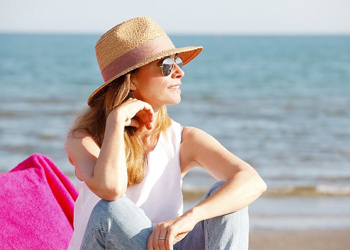 woman-enjoying-sunshine-while-relaxing-on-the-beach
