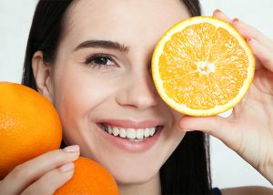 happy woman holding oranges near her face